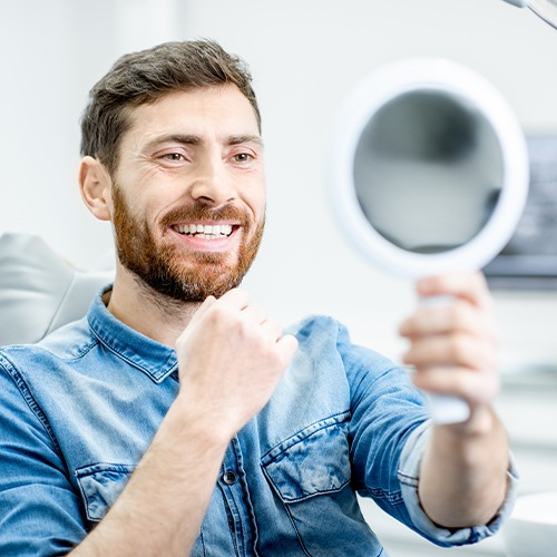 Man looking at his smile after one visit dental restoration placement