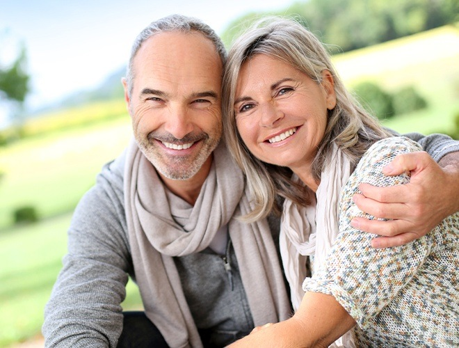 Older man and woman with beautiful smiles thanks to cosmetic dentistry