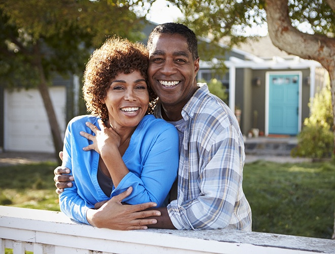 Older couple laughing together after replacing teeth with dental implants