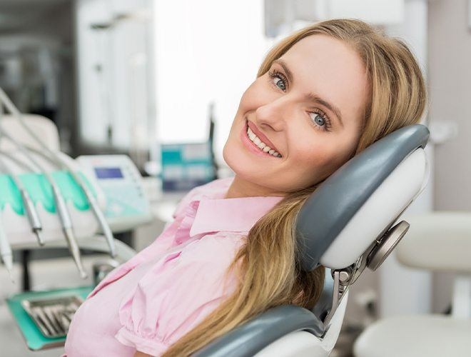 Woman smiling after pain relieving root canal therapy