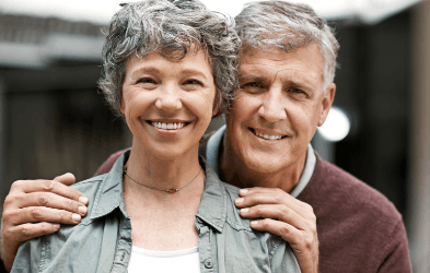Older couple smiling after replacing missing teeth